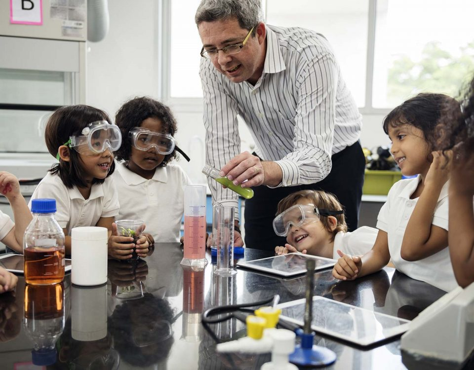 A teacher demonstrates a chemical reaction in front of students wearing safety goggles.