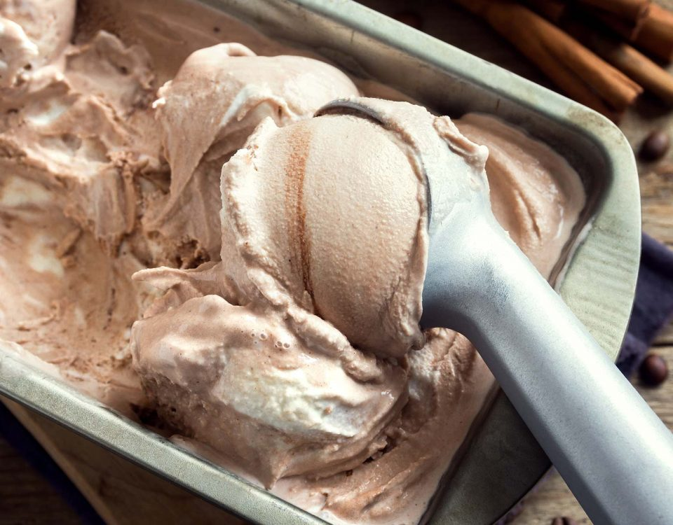 An ice cream scoop is used to scoop chocolate ice cream from a metal container.