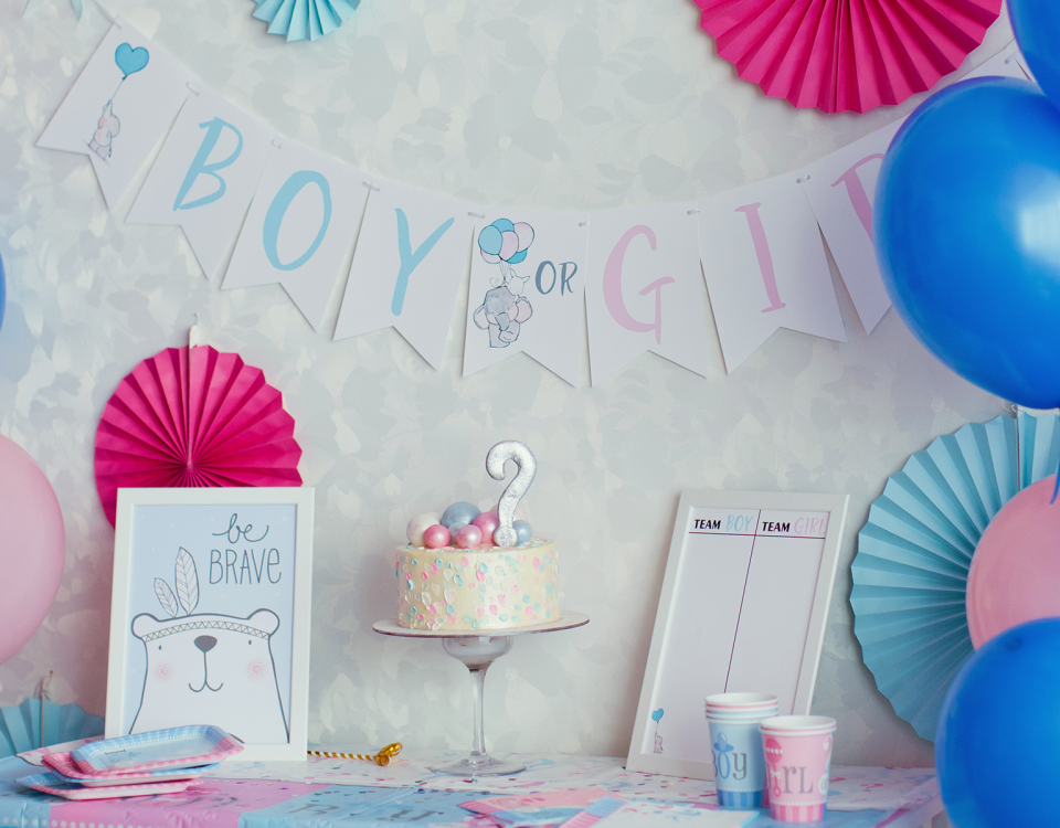 "A ""Boy or Girl?"" sign hangs on the wall behind a cake and festive decor for a gender reveal party"