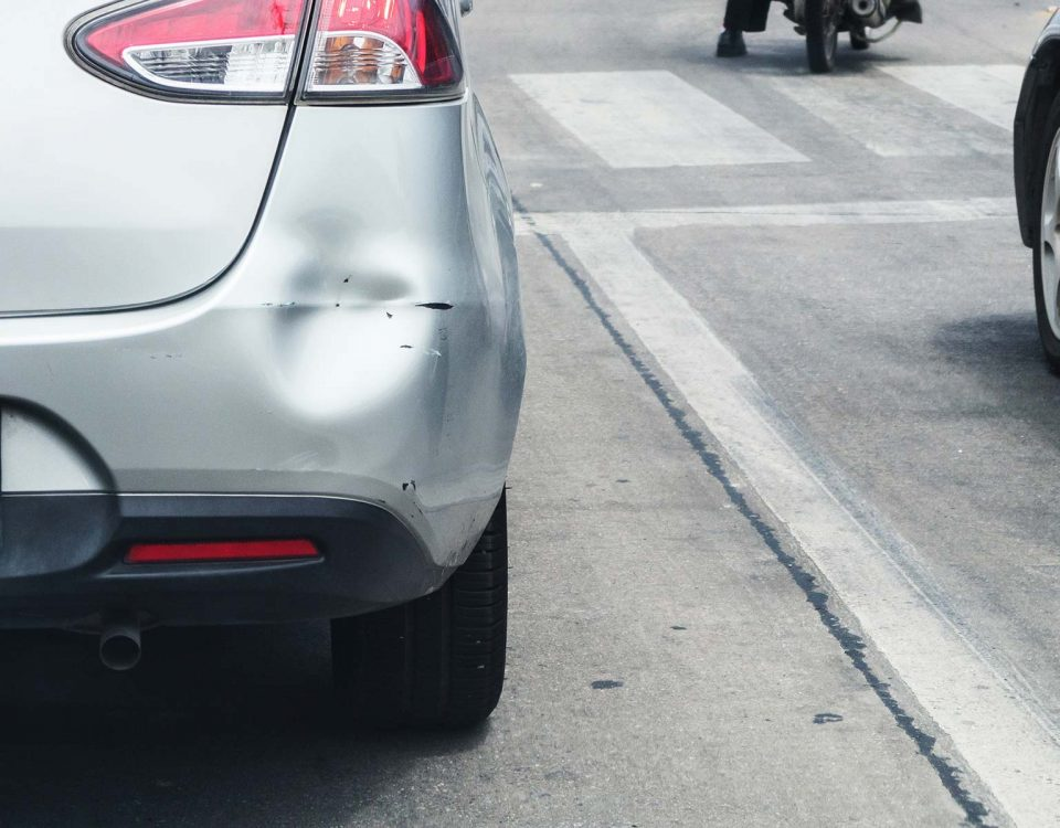 A large dent in a the bumper of a silver sedan-style car is shown
