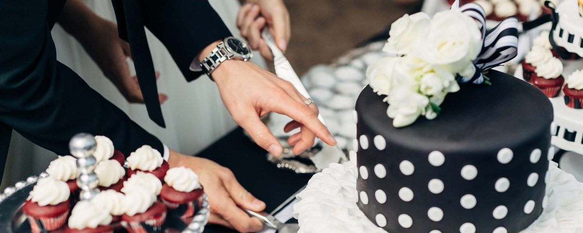 A newly wedded couple prepares to cut into their wedding cake.